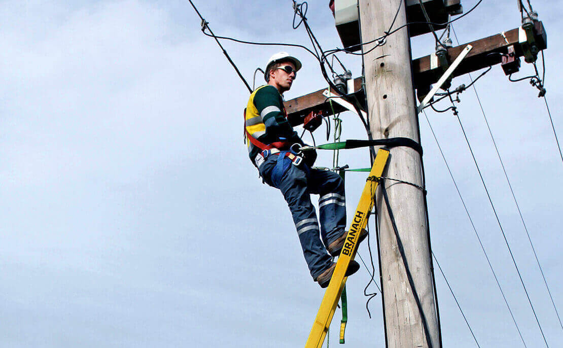 Electrical worker high up on a power pole using the fibreglass PowerMaster Extension ladder.