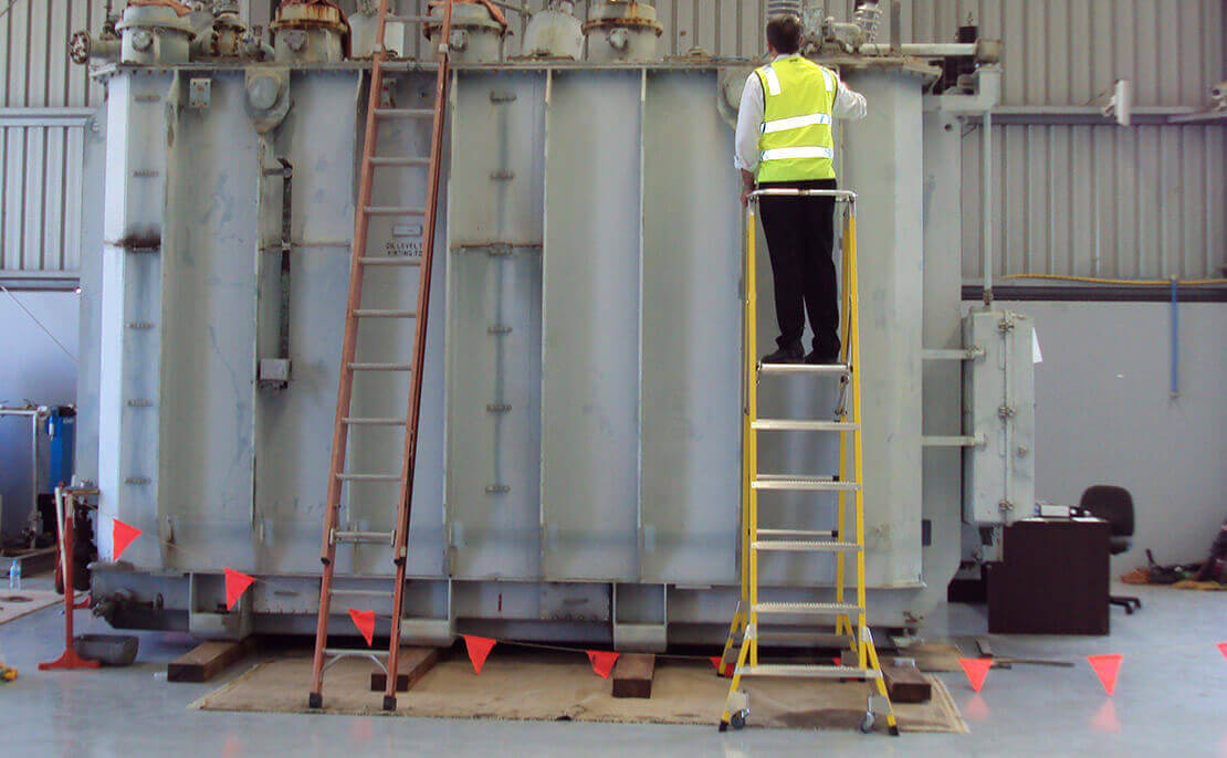 Worker using the fibreglass WorkMaster 550mm Step Platform ladder to complete inspections within a factory.