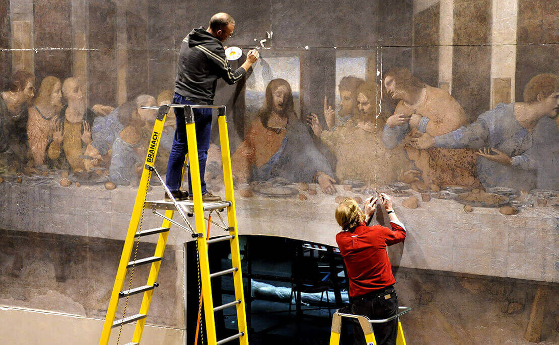 2 people using the fibreglass WorkMaster 550mm Step Platform ladders to carry out restoration of 'The Last Supper' replica painting.