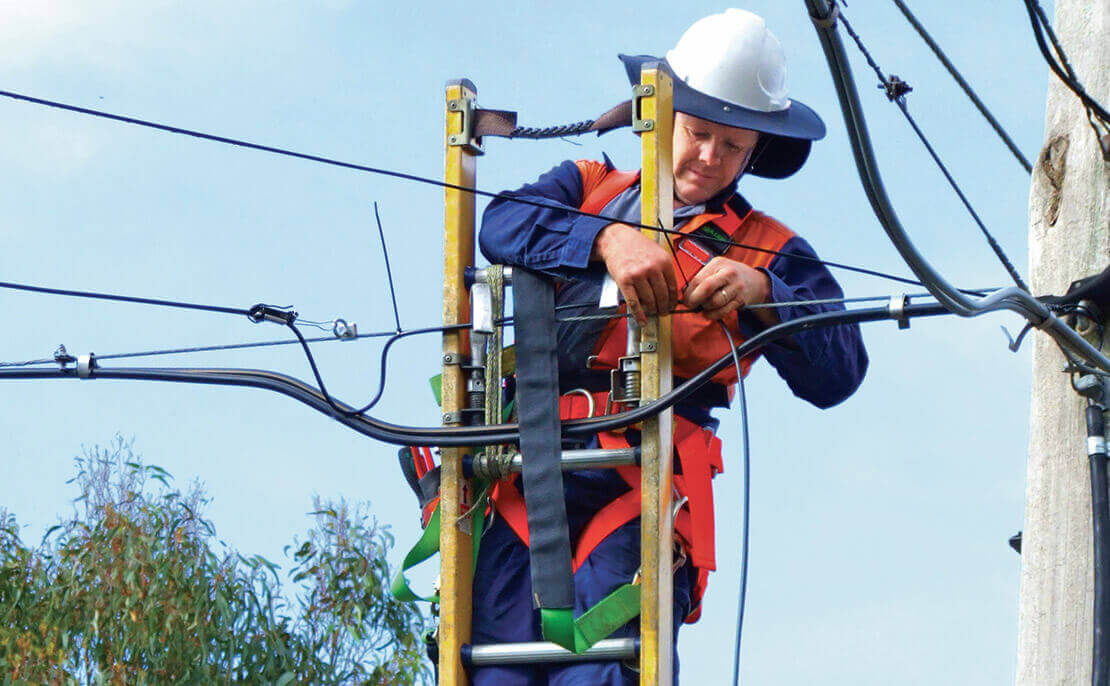 Telecommunications worker using the fibreglass PowerMaster Extension ladder to check overhead fibreoptic cable.