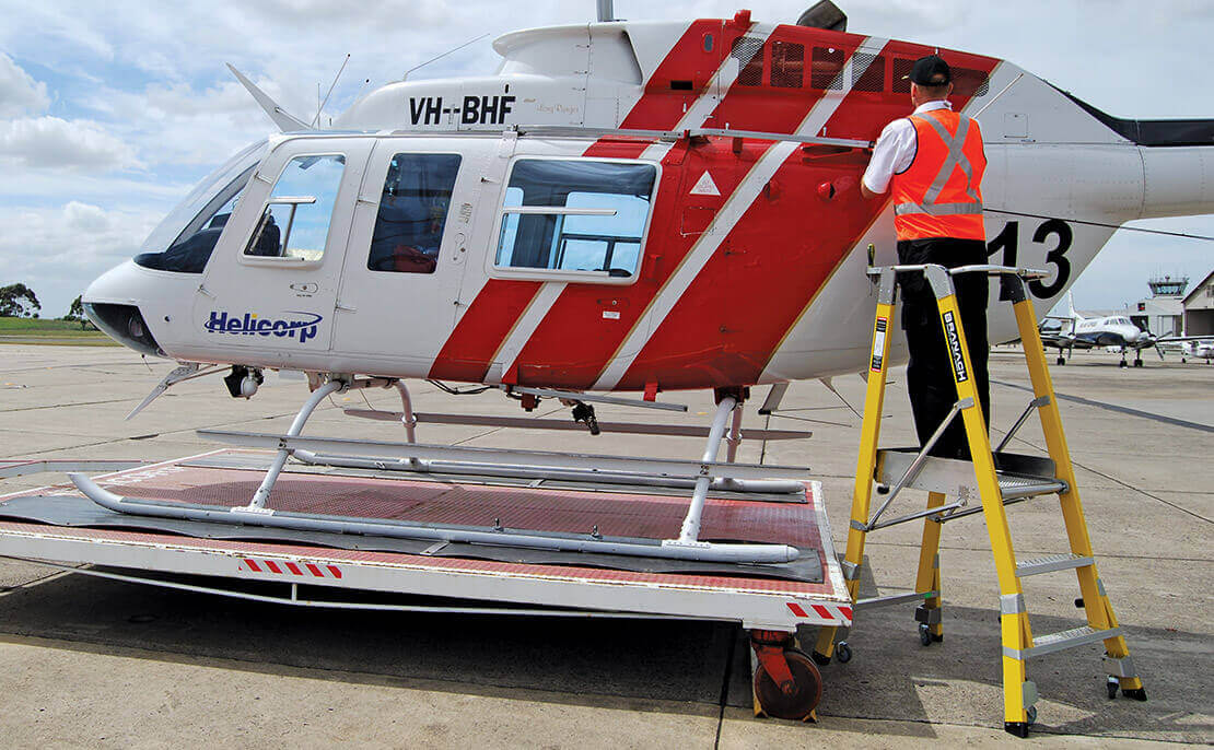 The fibreglass WorkMaster 550mm Step Platform ladder being used to inspect the top of a helicopter.