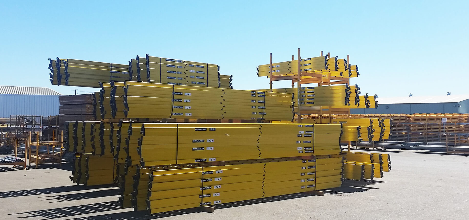 A large pile of Branach fibreglass PowerMaster Single Ladders.