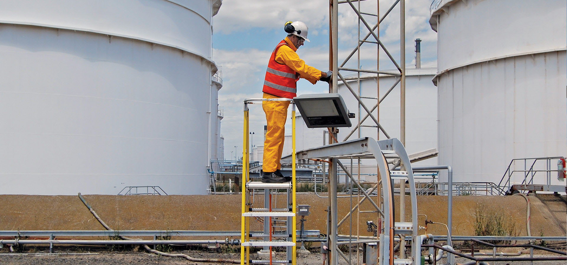 A refinery worker standing on the Branach fibreglass WorkMaster 550mm Step Platform Ladder.